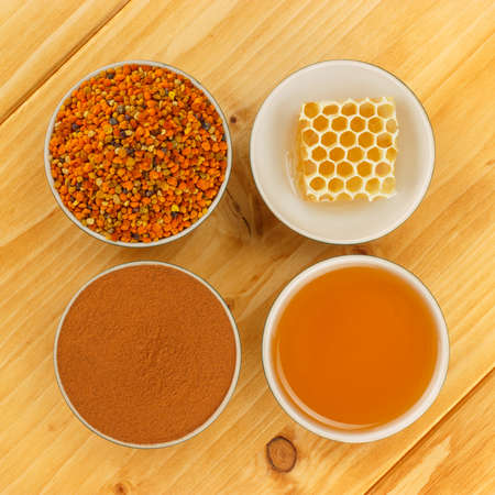 Honey, honeycomb, pollen granules and cinnamon in porcelain bowls, seen from above, on wooden tabletop surface photo