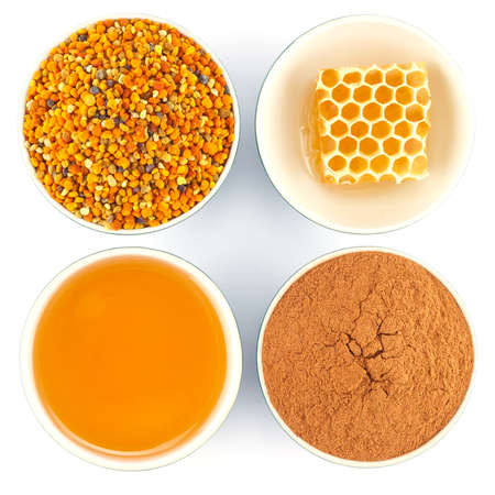 Honey, honeycomb, pollen granules and cinnamon in green porcelain bowls, seen from above, on white isolated background photo
