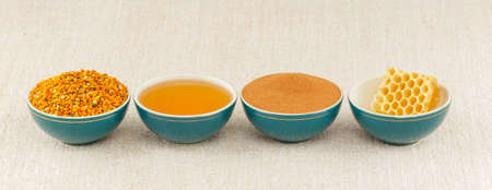 antiviral: Honey, honeycomb, pollen granules and cinnamon in green porcelain bowls in a row, on rustic table cloth