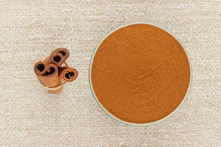 antiviral: Ground cinnamon powder in green porcelain bowl and cinnamon sticks on rustic table cloth, seen from above Stock Photo