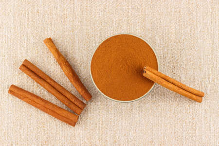 antimicrobial: Ground cinnamon powder in green porcelain bowl and cinnamon sticks on rustic table cloth, seen from above Stock Photo