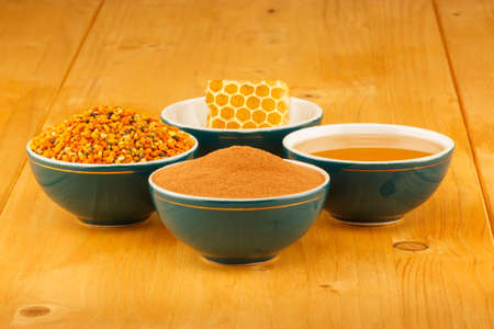 Honey, honeycomb, pollen granules and cinnamon in green porcelain bowls, on wooden tabletop surface photo