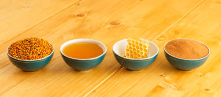 Honey, honeycomb, pollen granules and cinnamon in green porcelain bowls in a row, on wooden tabletop surface photo
