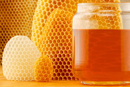 honey comb: Honey in glass jar, with honeycomb background on wooden rustic tabletop