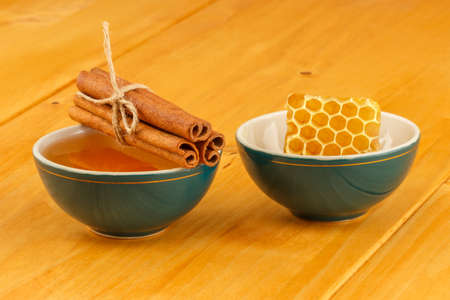 Honey, honeycomb and cinnamon sticks in two green porcelain bowls on wooden tabletop surface photo