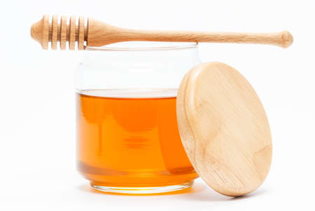 honey jar: Honey in glass jar with wooden dipper and cap on white isolated background Stock Photo
