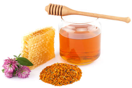 Honey in glass jar with wooden dipper, honeycomb, pollen granules and clover flowers on white isolated background photo