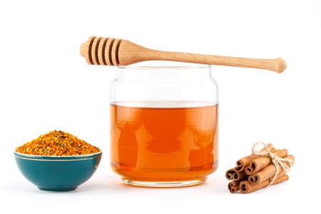 Honey in glass jar with wooden dipper, cinnamon sticks, pollen granules in porcelain bowl  on white isolated background photo