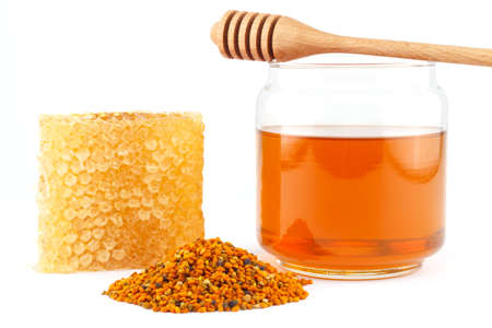 Honey in glass jar with wooden dipper, honeycomb and pollen granules on white isolated background photo