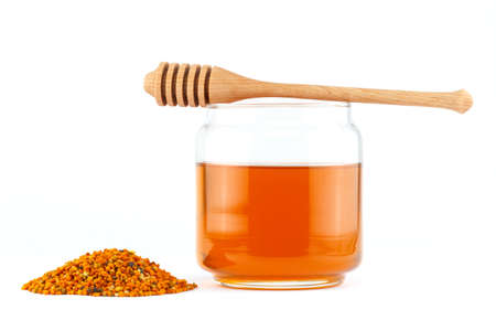 Honey in glass jar with wooden dipper and pollen granules on white isolated background photo