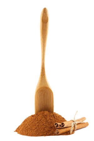 Ground cinnamon powder and sticks, with bamboo gauge scoop on white isolated background photo