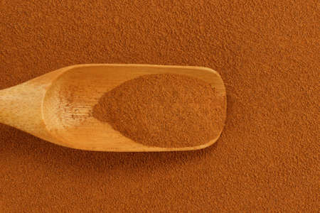 antiviral: Ground cinnamon powder and bamboo gauge scoop Stock Photo