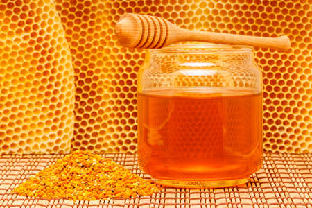 Honey in glass jar with wooden dipper and pollen granules on light rustic mat with honeycomb  photo