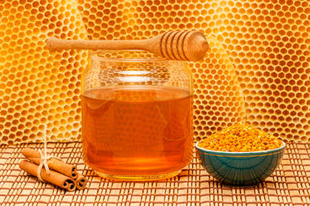 Honey in glass jar with wooden dipper, cinnamon sticks and pollen granules in green porcelain bowl on light rustic mat with honeycomb  photo