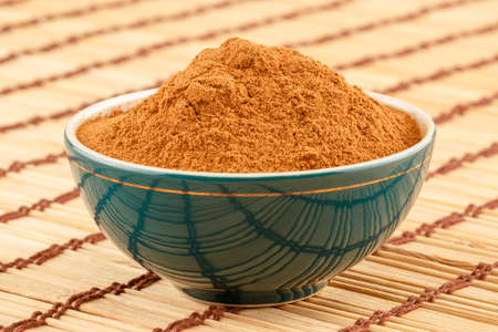 antiviral: Ground cinnamon powder in green porcelain bowl on light rustic mat