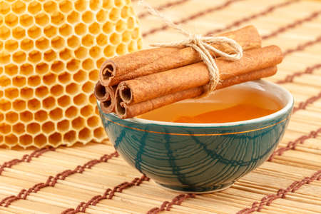 Honey in green porcelain bowl, with honeycomb and cinnamon sticks on light rustic mat Stock Photo