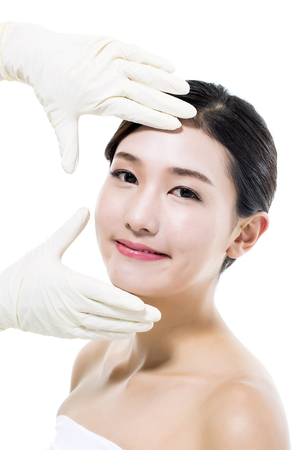 Plastic Surgery Doctor Examining the Face of a Young Asian Woman Stock Photo