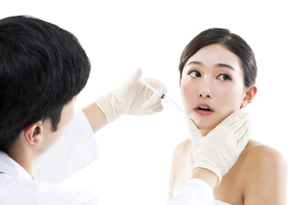Plastic Surgery/ Young Asian Woman Receiving an Injection of Botox from a Doctor