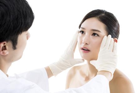 성형 외과  의사는 젊은 아시아 여자의 얼굴을 검사