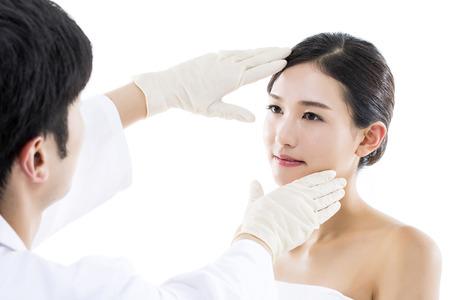 整形外科医師がアジアの若い女性の顔を調べる 写真素材