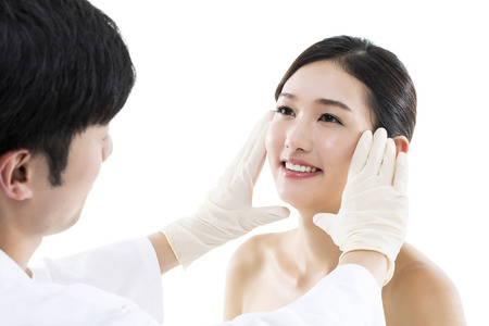 Plastic Surgery Doctor Examining the Face of a Young Asian Woman Banco de Imagens