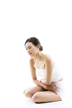 Asian Woman Suffering From Her Menstrual Crampsstomach pain - Isolated on White Stock Photo
