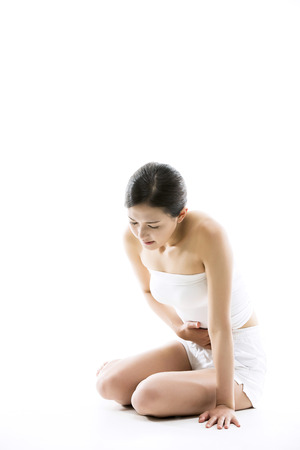 menstrual pain: Asian Woman Suffering From Her Menstrual Crampsstomach pain - Isolated on White Stock Photo