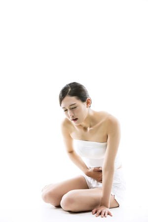 menstrual: Asian Woman Suffering From Her Menstrual Crampsstomach pain - Isolated on White Stock Photo