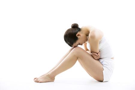 Mujer asiática que sufre de dolor de ella calambres menstruales  estómago - aislado en blanco Foto de archivo