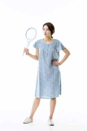 Asian Girl in Pajamas Trying to Catch Mosquittoes Stock Photo