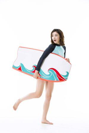 side shot: Beautiful Asian Woman in Rash Guard Surfers Outfit