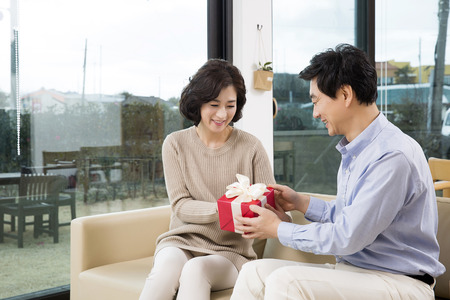 korean style house: Middleaged Asian Man Giving a Red Gift Box to his Wife in the Living room