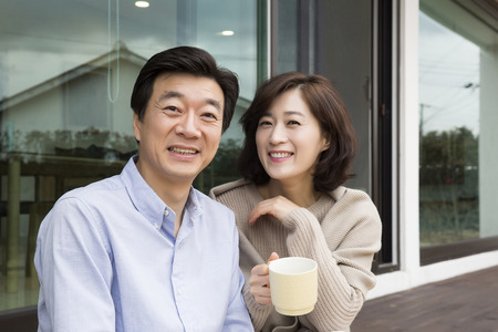 Middleaged Asian Couple Sitting, Having coffee at Porch