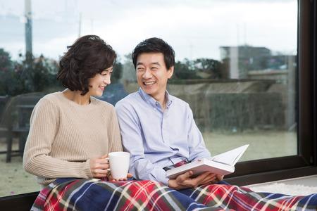笑みを浮かべて、リビング ルームに座っている中年アジア カップル