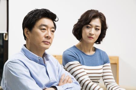 argumento: Pareja asiática de mediana edad que tienen un argumento en la sala de estar