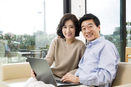 リビングでノート パソコンを見て中年アジア カップル