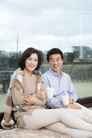 Middleaged Asian Couple Smiling and Sitting with Coffee Mugs on Rug In Livingroom Фото со стока