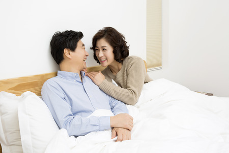 Middleaged Asian Couple Smiling Together in Bed Stock Photo
