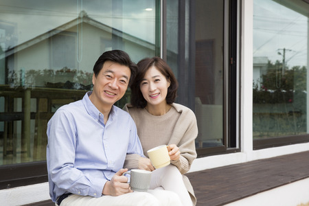 Middleaged Asian Couple Sitting, tomando un café en el porche Foto de archivo - 66108521