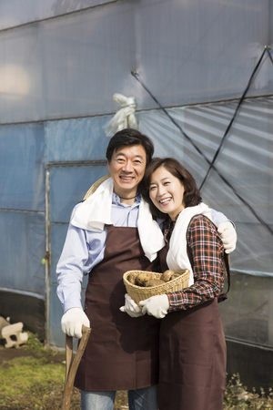 conservatory: Middleaged Asian Couple Working on Field Stock Photo