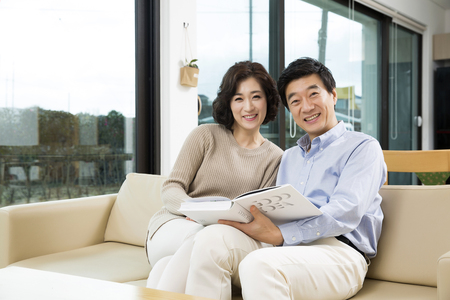 Middleaged Asian Couple Smiling in the Living room Imagens