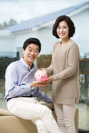 Happy Middleaged Asian Couple Holding a Piggy Bank