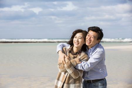 ビーチに笑みを浮かべて中年アジア カップル