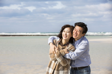 Middleaged Asian Couple Smiling on Beach 스톡 콘텐츠