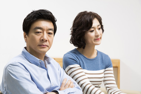 Middleaged Asian Couple Having an Argument in Livingroom Фото со стока - 66108725