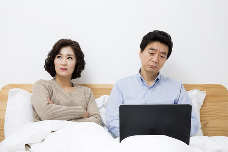 Middleaged Asian Couple Looking stressed in Bedroom with Laptop