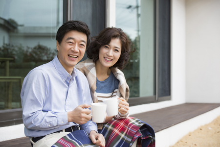 Middleaged Asian Couple Smiling and Sitting with Coffee Mugs on Porch