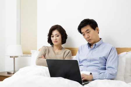 korean style house: Middleaged Asian Couple Looking stressed in Bedroom with Laptop