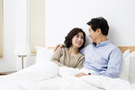 korean style house: Middleaged Asian Couple Smiling in Bed Stock Photo