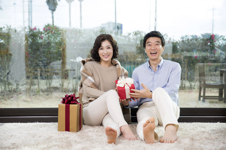 Middleaged Asian Couple Smiling and Sitting with Gift Boxes on Rug In Livingroom Stock Photo